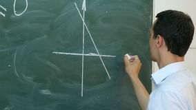 Young teacher or student draw line chart on a blackboard with formula royalty free stock image