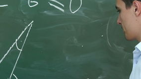 Young teacher or student draw triangle on a blackboard with formula stock video footage
