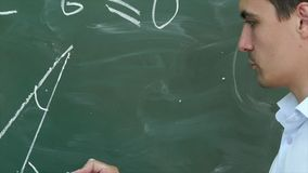 Young teacher or student draw triangle on a blackboard with formula. Professional shot on Lumix GH4 in with high 4K resolution. You can use it e.g in your Royalty Free Stock Photography
