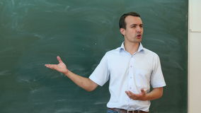 Young teacher or student tell something near the blackboard and gesticulate. stock video footage