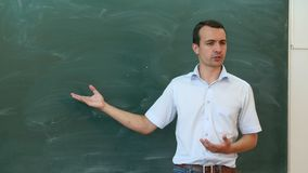 Young teacher or student tell something near the blackboard and gesticulate. Professional shot on Lumix GH4 in with high 4K resolution. You can use it e.g in Royalty Free Stock Photo