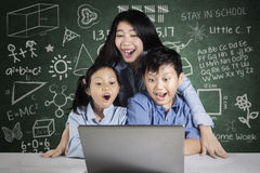 Young teacher and students look at laptop Stock Photos
