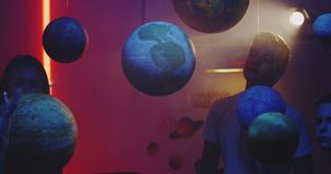 Young teacher teaching astronomy with planet models. Medium shot of a female teacher explaining astronomy to students with suspended planet models stock footage
