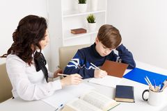 Young teacher trying to explain information to the boy. Educating together. Young teacher trying to explain information to the boy. Educating together stock photo