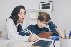 Young teacher trying to explain information to the boy. Educating together. Young teacher trying to explain information to the boy. Educating together royalty free stock photo
