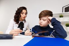 Young teacher trying to explain information to the boy. Educating together. Young teacher trying to explain information to the boy. Educating together stock photography