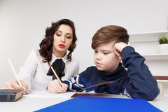 Young teacher trying to explain information to the boy. Educating together. Young teacher trying to explain information to the boy. Educating together royalty free stock image