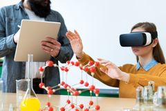 Young teacher using Virtual Reality Glasses and 3D presentation to teach students in chemistry class. Education, VR, Tutoring. Young teacher using Virtual Royalty Free Stock Photography