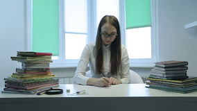 Young teacher in white shirt writes in copybook at desk in classroom. stock video footage