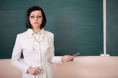 Young teacher woman on green board Stock Image
