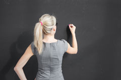 Young teacher writing with white chalk on empty blackboard in classroom Royalty Free Stock Photos