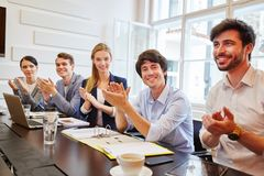 Young team applause in meeting. During successful presentation royalty free stock photo