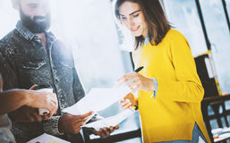 Young team of coworkers making great discussion in sunny office near the window.Woman signing the papers. Horizontal Royalty Free Stock Images