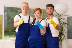 Young team of house cleaners. Showing thumbs up royalty free stock photography