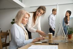 Young team leader correcting offended senior employee scolding f. Young team leader correcting offended senior employee working on computer in office, female Stock Images
