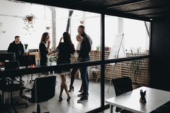 Young team stand together and talk behind the glass wall in the spacious light modern office equipped with modern stock photo