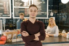 Young team of three cafe workers, people posing and smiling at coffee bar near bar counter. Teamwork, staff, small business, royalty free stock photos
