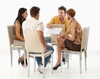 Young team working on project. Sitting in circle Royalty Free Stock Photography