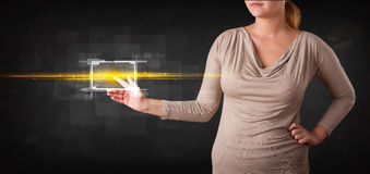 Young tech lady touching button with orange light beams concept Royalty Free Stock Images