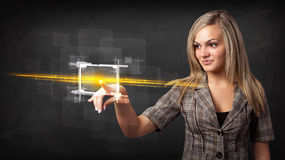 Young tech lady touching button with orange light beams concept Royalty Free Stock Photography