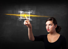Young tech lady touching button with orange light beams concept Stock Photo