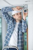 Young technician adjusting cctv camera on wall. Fitting royalty free stock photos