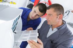 Young technician apprentice repairing ac with teacher. Apprentice Stock Images