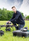 Young Technician Assembling UAV in Park. Portrait of confident young technician assembling UAV drone in park royalty free stock photos