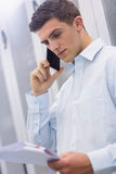 Young technician calling and reading a document Royalty Free Stock Images