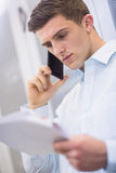 Young technician calling and reading a document Stock Photos