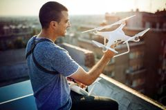 Young technician flying UAV drone with remote control on rooftop stock photography
