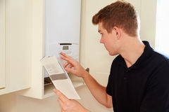 Young technician servicing a boiler, consulting manual Stock Image