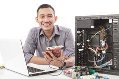 young technician smiling while fixing computer hardware Stock Photos