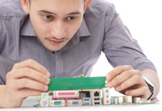 Young technician unstalling ram memory to motherboard Stock Photo