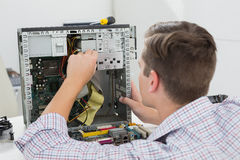 Young technician working on broken computer Stock Images
