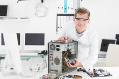 Young technician working on broken computer. In his office Stock Photos