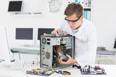 Young technician working on broken computer Stock Photo
