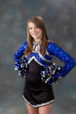 Young teen age cheer leader. Portrait of a pretty teen age cheer leader standing in front of blue background stock images