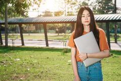 A young or teen asian girl student in university. And holding the laptop computer in summer holiday in the park Royalty Free Stock Photo