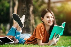 A young or teen asian girl student in university. Smiling and reading the book and look at the tablet or laptop computer in summer holiday Stock Image
