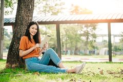 A young or teen asian girl student in university smiling and reading the book and look at the tablet. Or laptop computer in summer holiday Royalty Free Stock Photo