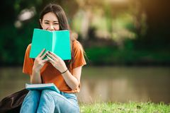 A young or teen asian girl student in university. Smiling and reading the book and look at the tablet or laptop computer in summer holiday Royalty Free Stock Image