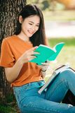 A young or teen Asian girl student in university. Smiling and reading the book and look at the tablet or laptop computer in summer holiday Royalty Free Stock Photo