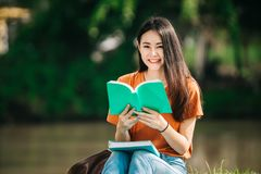 A young or teen asian girl student in university. Smiling and reading the book and look at the tablet or laptop computer in summer holiday Royalty Free Stock Images