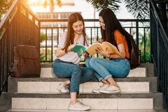 Young or teen Asian student in university. A group of young or teen Asian student in university smiling and reading the book and look at the tablet or laptop royalty free stock images