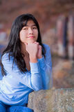 Young teen biracial girl quietly resting elbows on rock along lake shore Royalty Free Stock Image