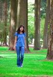 Young teen biracial girl walking under tall trees Royalty Free Stock Image