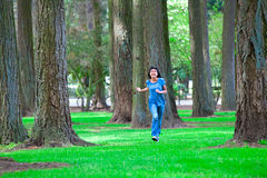 Young teen biracial girl walking under tall trees Royalty Free Stock Photography