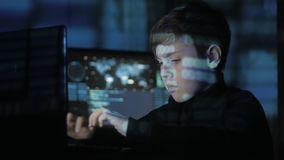 Cute teen Boy hacker programmer is working on computer in cyber security center filled with display screens. Binary code. Young Teen Boy hacker programmer is stock video