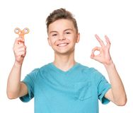 Teen boy with spinner toy. Young teen boy holding popular fidget spinner toy and making ok gesture. Happy smiling child playing with Spinner, isolated on white Stock Photo